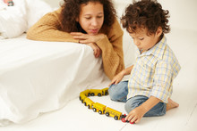 Indoor Shot Of Happy Young Latin Woman In Sweater Watching Her Infant Son Play With Toy Railway On Floor In Bedroom, Not Distracting Him. Maternity, Child Care, Early Development And Imagination