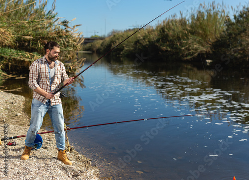 Canvas Prints Fishing Happy fisherman pulls fish out of the river