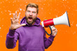 Leinwandbild Motiv young blonde man with a megaphone  wearing a purple hoodie against damaged orange wall
