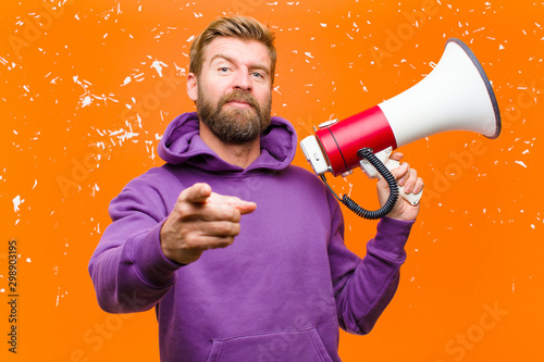 Photo young blonde man with a megaphone  wearing a purple hoodie against damaged orang