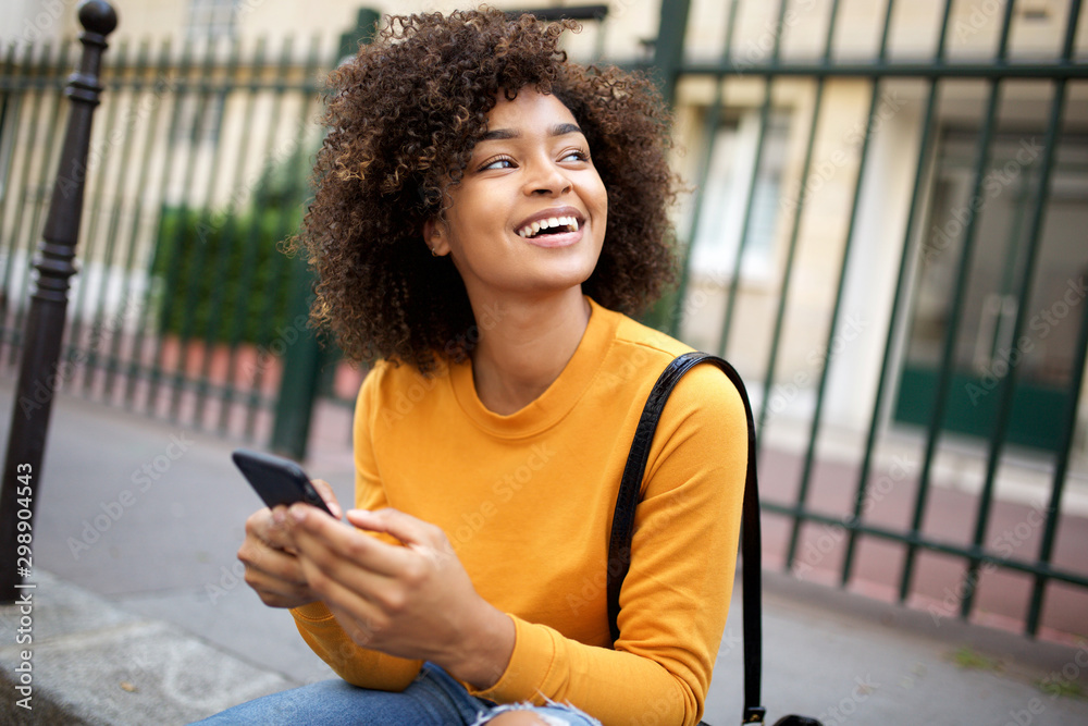 Fototapety, obrazy: happy african american young woman holding cellphone and looking away