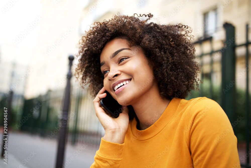 Fototapeta happy african american young woman talking with cellphone in city