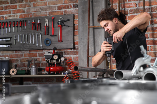 Obraz man in home workshop garage work drilling metal with drill, repair iron pipe on the workbench full of wrenches, diy and craft concept - fototapety do salonu