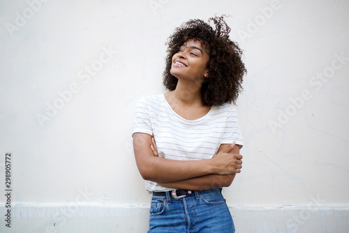 Fotografiet  happy young african american woman smiling with arms crossed and looking away ag