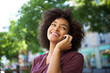 young smiling african american woman talking with cellphone outdoors