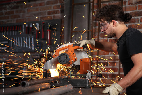 Valokuvatapetti man work in home workshop garage with miter saw, goggles and construction gloves
