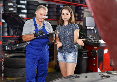 Fotografía  Mechanic with client recording workslist on car repair