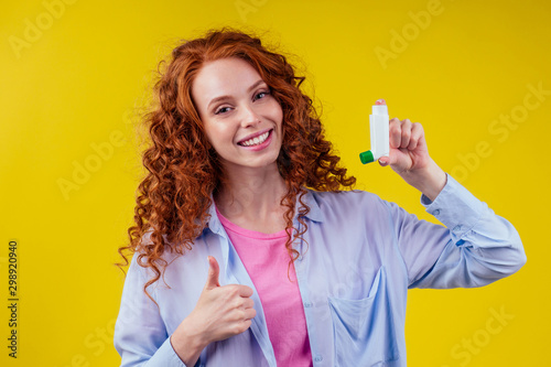 Fototapeta happy redhead curly ginger woman showing thumbs up pointing in studio yellow background obraz