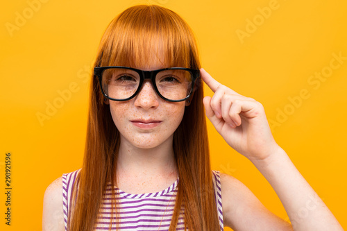 Fotografía  red-haired teenager in the background of an orange wall with glasses for vision