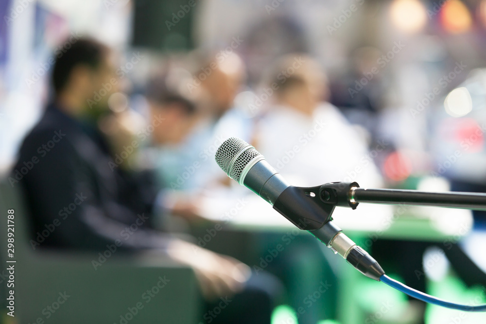 Fototapeta Microphone in focus against blurred people at roundtable event
