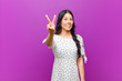 canvas print picture - young pretty latin woman smiling and looking friendly, showing number two or second with hand forward, counting down against purple wall