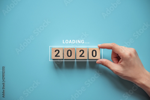 Obraz Loading new year 2020 with hand putting wood cube in progress bar. - fototapety do salonu