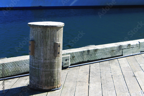 Photo Wooden bollard on a wooden pier, harbour side