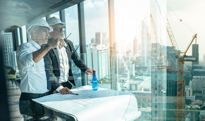 Two Engineer or Architect are analyzing blueprints while working on a new project on construction site with blue sky and city background.Architect supervising construction on terrace tower.