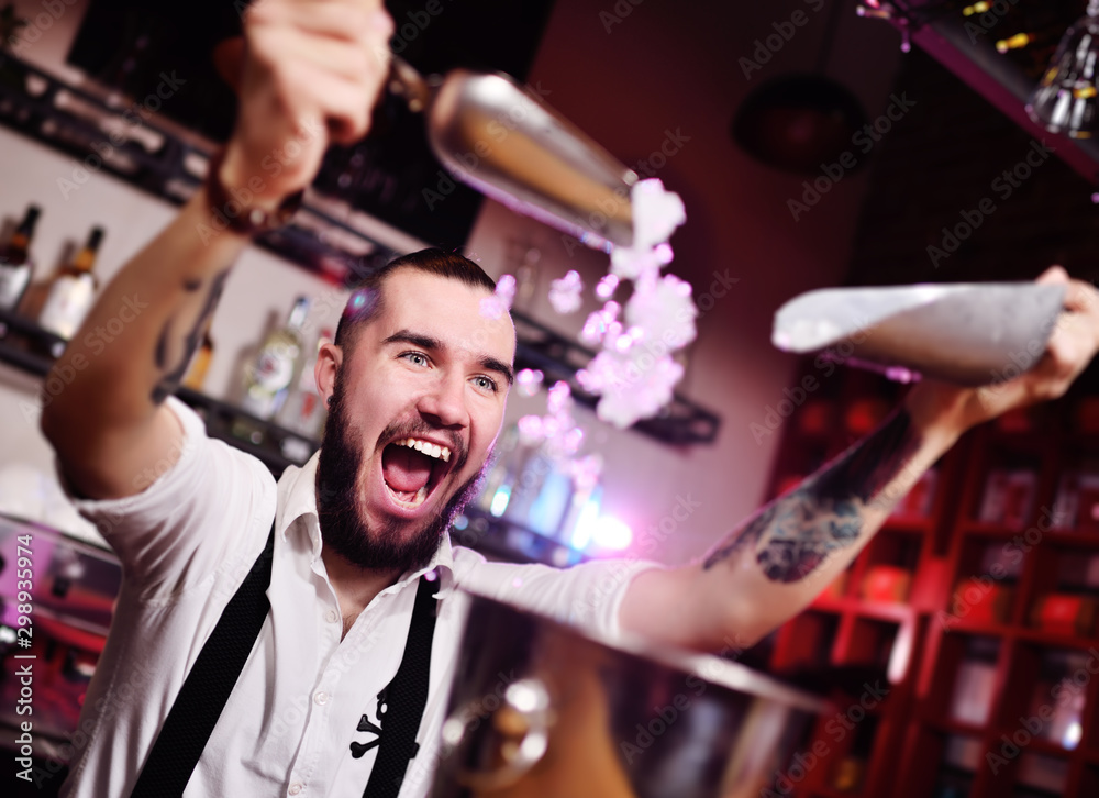 Fototapety, obrazy: a handsome bearded bartender in a white shirt pours ice for cocktails and screams happily against the bar at a nightclub party