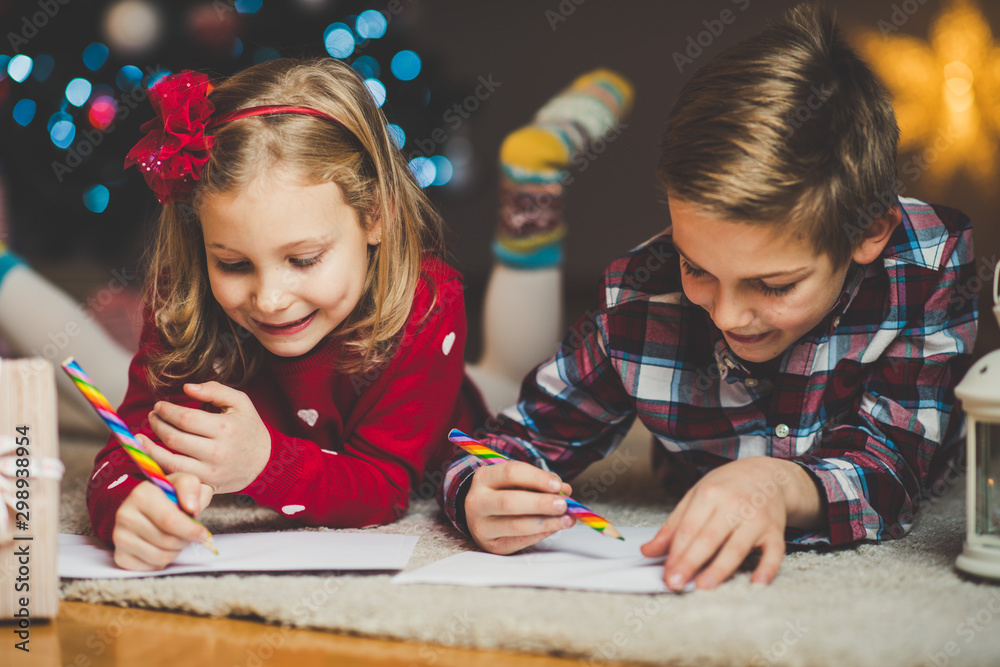 Fototapeta Two happy children writing letter to Santa Claus at home near New Year tree