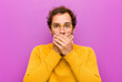 canvas print picture - young handsome man covering mouth with hands with a shocked, surprised expression, keeping a secret or saying oops against purple wall