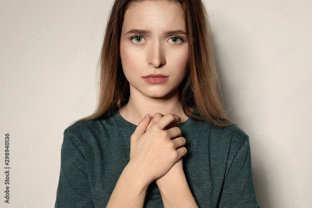Fototapety, obrazy: Portrait of upset young woman on light background
