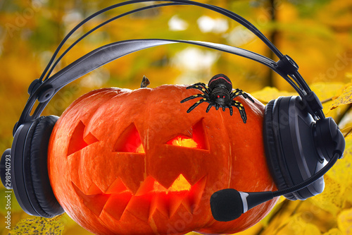Halloween orange musical pumpkin in headphones with bright glowing eyes and a sp Canvas Print