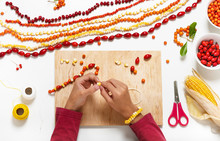 Little Child Hands Make Necklace With Colorful Seeds And Forest Berries. Kids Nature Crafts. Children Education Concept.