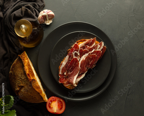 Toasted bread with Iberian ham on black plates and rustic background - zenith vi Canvas Print