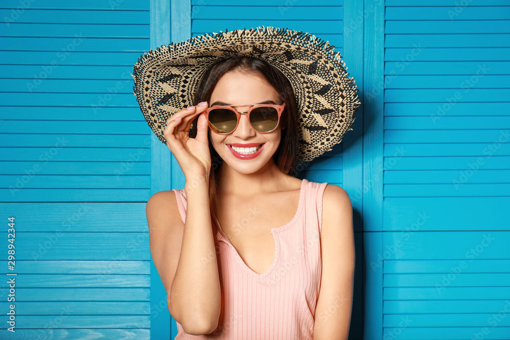 Fototapeta Beautiful woman wearing sunglasses and hat near blue wooden folding screen