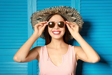 Beautiful Woman Wearing Sunglasses And Hat Near Blue Wooden Folding Screen