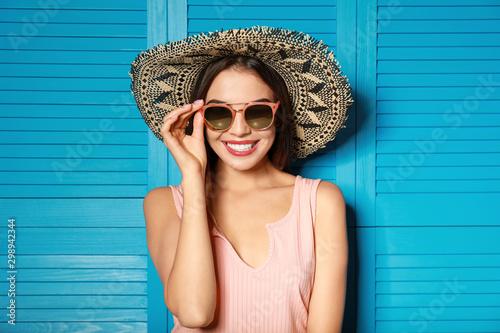Obraz Beautiful woman wearing sunglasses and hat near blue wooden folding screen - fototapety do salonu