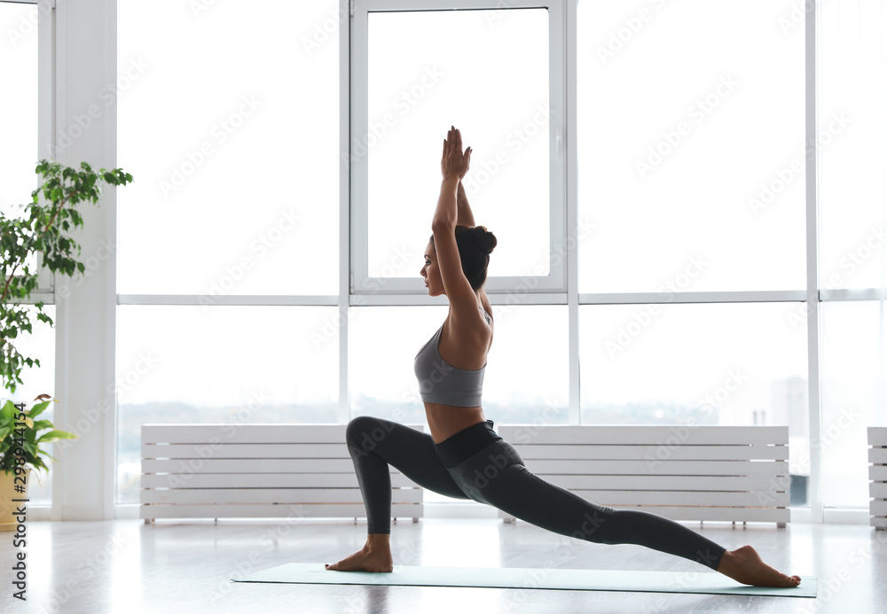 Fototapety, obrazy: Young woman practicing crescent pose in yoga studio