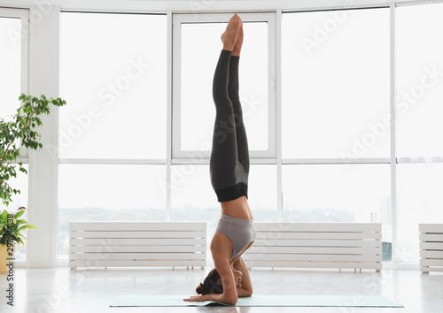 Young woman practicing supported headstand asana in yoga studio Canvas Print
