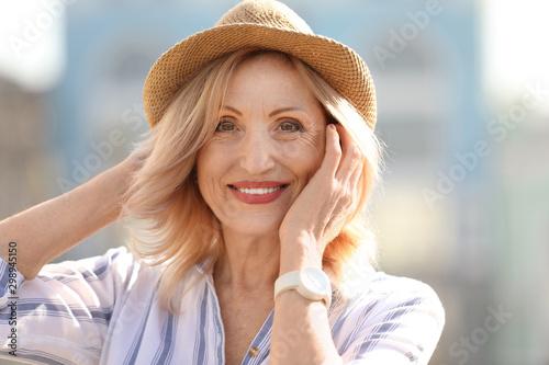 fototapeta na lodówkę Portrait of happy mature woman on city street