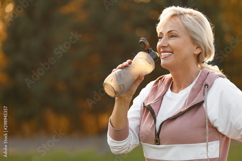 Fototapeta Sporty mature woman with bottle of water outdoors obraz na płótnie