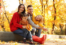 Happy Family With Little Daughters In Park. Autumn Walk