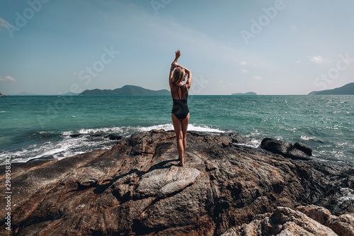 Foto auf Gartenposter Cappuccino .Woman in black swim suit on a cliff by the ocean in a sunny day, her arms above her head, back side view, silhouette..