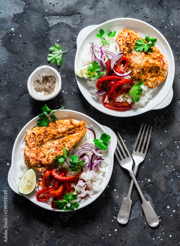 Fotomural  Baked spicy chicken breast with sweet pepper and rice -  delicious mexican style lunch on a dark background, top view