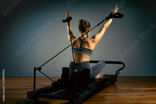 Fotografia  Young girl doing pilates exercises with a reformer bed