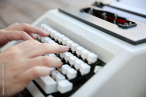 Manos de persona tecleando en máquina de escribir vintage en mesa de madera vist Canvas Print