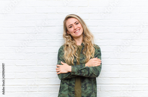 young blonde woman laughing happily with arms crossed, with a relaxed, positive Canvas Print