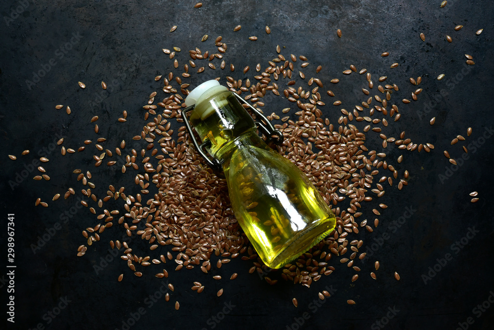 Fototapety, obrazy: Linseed oil in a bottle and flax seed. Top view with copy space.