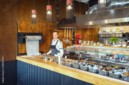 Leinwand Poster Successful small business owner woman standing behind counter of newly opened re