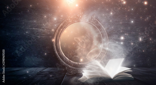 An open book and a magic mirror against the backdrop of a night landscape Fototapeta
