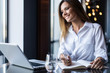 Brunette Business woman working with papers near window in cafe