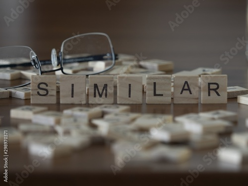 Fotografie, Tablou  The concept of Similar represented by wooden letter tiles