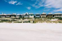 Beach Front Homes On White Sand With Blue Sky