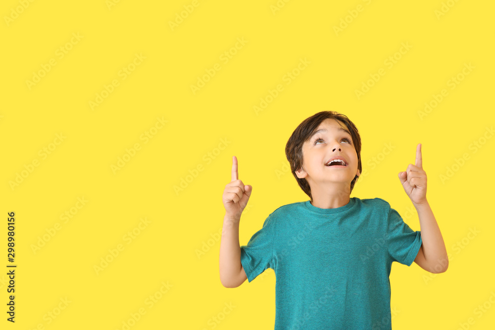 Fototapety, obrazy: Happy little boy pointing at something on color background