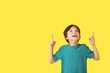 canvas print picture - Happy little boy pointing at something on color background