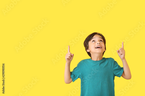 Fotografía  Happy little boy pointing at something on color background