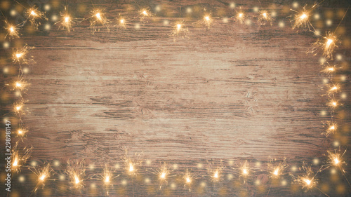 Photo  frame of lights bokeh flares and sparkler isolated on rustic brown wooden textur