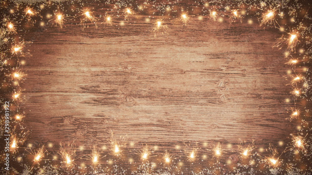 Fototapeta frame of lights bokeh flares and sparkler isolated on rustic brown wooden texture - holiday New Year's Eve background banner