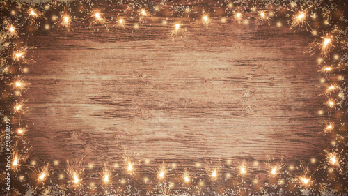 Fototapeta frame of lights bokeh flares and sparkler isolated on rustic brown wooden texture - holiday New Year's Eve background banner   obraz